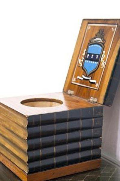 Inodoro portátil en forma de pila de libros que llevan el título escrito. Sulabh International Museum of Toilets.